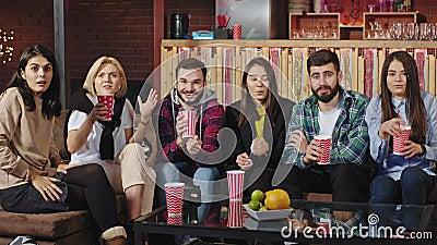 Los amigos carismáticos concentrados tienen una noche de cine viendo una película de horror en un televisor que tienen miedo de d almacen de metraje de vídeo