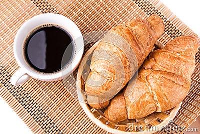 Los croissants franceses frescos y sabrosos en una cesta y una taza de café sirvieron