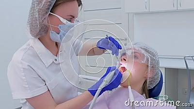 Los dientes de la mujer pulidora limpiadora y cepillado usan taladro en odontología metrajes