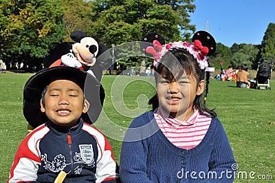 Los hermanos con el sombrero de Mickey y el pelo grandes de Minnie congriegan Imagen de archivo editorial