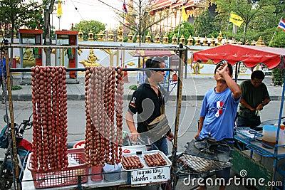 Los hombres tailandeses venden la carne de salchicha en Bangkok, Tailandia. Imagen de archivo editorial