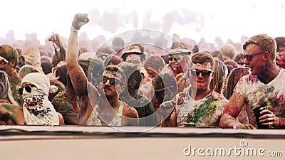Los individuos blancos cubiertos en polvo bailan en el festival del color del holi en la cámara lenta