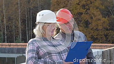 Los ingenieros de la mujer y del hombre en el emplazamiento de la obra se divierten que discuten el proyecto almacen de video
