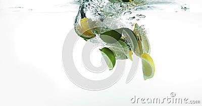 Los limones amarillos, Citrus Limonum, y los limones verdes, fruta cítrica aurantifolia, dan fruto cayendo en el agua contra el f almacen de metraje de vídeo