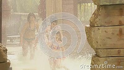 Los niños corren a través de spray para deslizarse en el parque acuático almacen de video