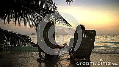 Los pares cariñosos en la playa tropical están admirando la puesta del sol y besarse metrajes
