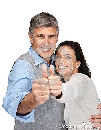 Los pares envejecidos medios felices que gesticulan los pulgares suben la muestra