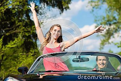 Los pares jovenes con el cabriolé en verano el día disparan
