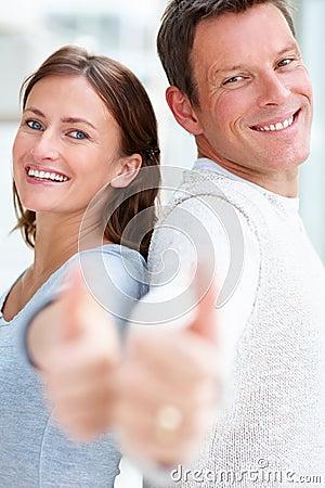 Los pares jovenes felices que muestran los pulgares suben la muestra