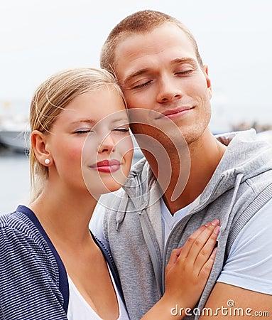 Los pares jovenes lindos que abrazaban con sus ojos se cerraron