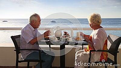 Los pares mayores desayunan en el hotel al aire libre