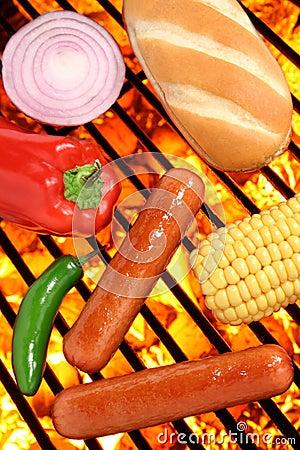 Los perritos calientes, el bollo y los veggies en barbacoa asan a la parilla