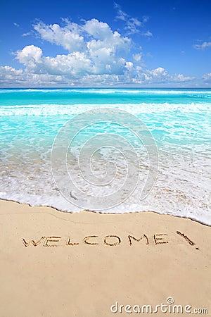 Los saludos dan la bienvenida al encanto de la playa escrito en la arena