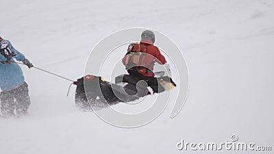 Los Snowboarders montan llevar a cabo encendido la cuerda de conducir moto de nieve Estación de esquí driver almacen de video