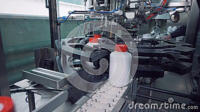 Los tarros plásticos blancos están consiguiendo cerrados mecánicamente con los casquillos almacen de metraje de vídeo