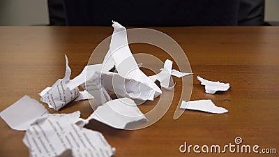Los trozos de papel rasgados caen en la tabla almacen de video
