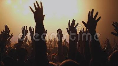 Lot of people clapping at rave party. Here is footage of people crowd partying at a concert or a night club. You can see dark silhouettes dancing, jumping and