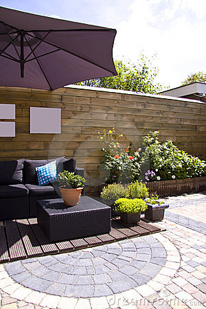 Lounge furniture on a wooden patio in a lovely garden with plants and