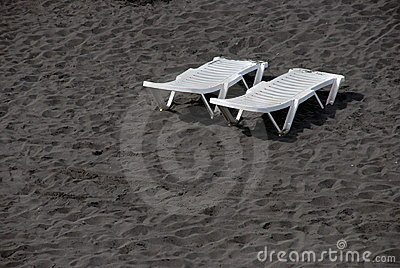 Lounge plastic white beds on black sand beach