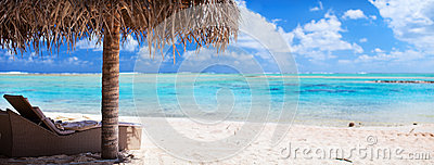 Loungers and umbrella on tropical beach