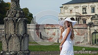 Louro em um vestido e em um chapéu brancos bonitos perto do video estoque