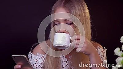 Louro novo em um fundo preto Bebe seu café e lê uma mensagem de texto em seu smartphone filme