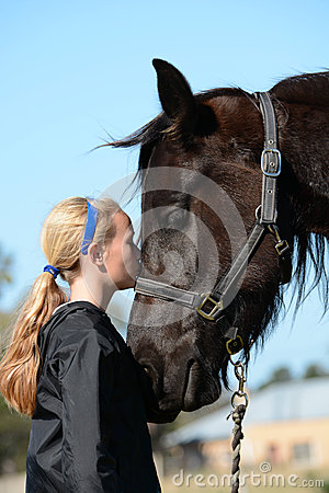 Girl kissing her pony
