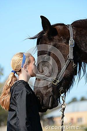Girl kissing her pony