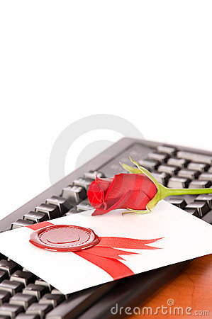 Love-letter and rose lying on black keyboard