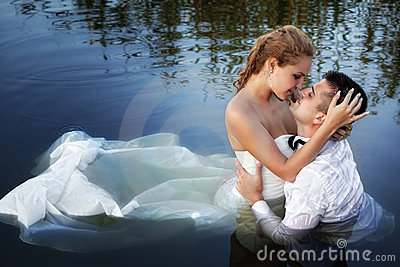 Love and passion - kiss of married couple in water