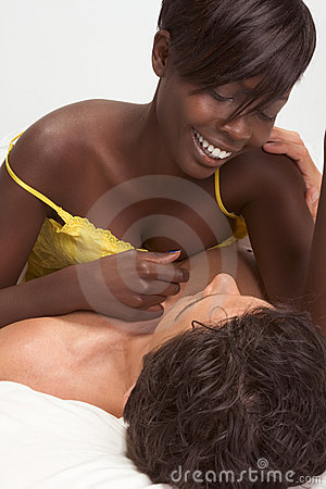 Love. Sensual interracial couple in bed loving