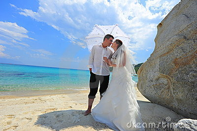 Love umbrella - newlyweds couple on exotic beach