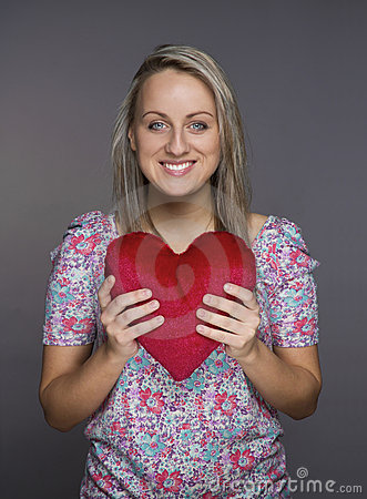 Lovely attractive girl with heart in hands
