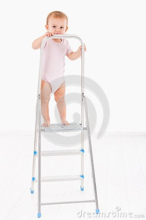 Lovely baby girl standing on top of ladder smiling