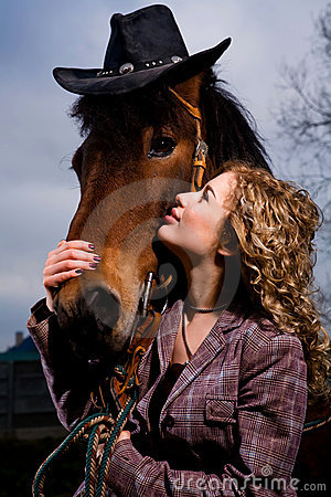 Lovely blond woman by horse