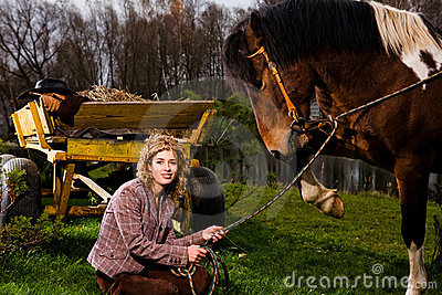 Lovely blond woman sitting by horse