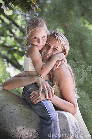 Lovely blonde young girl and mother hug outdoor