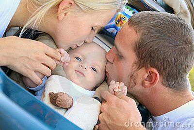 Lovely Caucasian Parents Kiss Their Baby Son