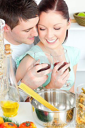 Lovely couple clinking glasses while cooking pasta