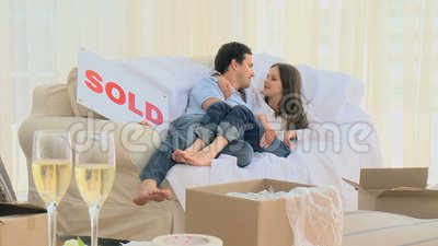 Lovely couple lying on the sofa and kissing each other Stock Photo