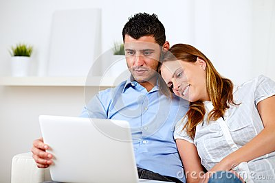 Lovely couple smiling and reading on laptop