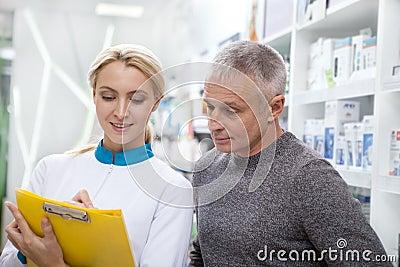 Lovely female pharmacist helping her client Stock Photo