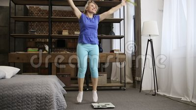 Lovely fit woman celebrating weight loss indoors stock video