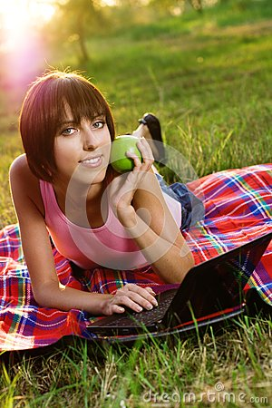 Lovely girl with laptop in the park