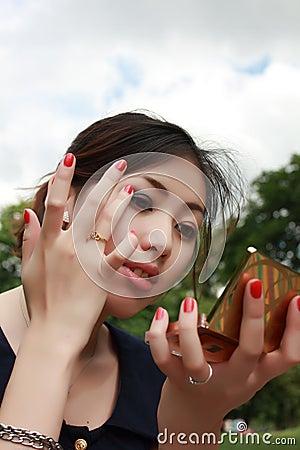 Lovely girl looks in mirror in the park