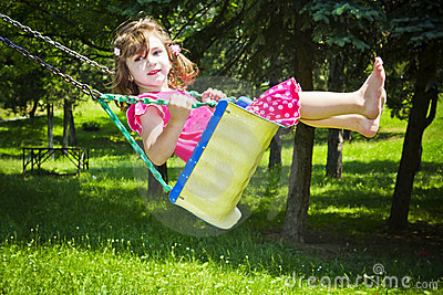 The lovely girl shakes on a swing