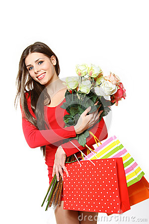 Lovely girl with shopping bags and roses on a white background