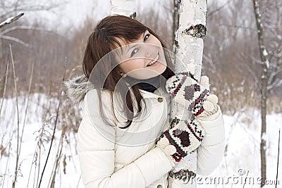 Lovely girl standing near birch