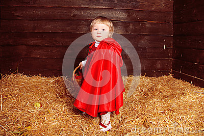 Lovely girl walking on pile of straw with a basket. Little Red R