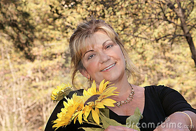 Lovely lady poses outdoors holding sunflowers